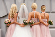 canvas print picture - Bride and bridesmaids in pink dresses posing with bouquets at wedding day. Happy marriage and wedding party concept