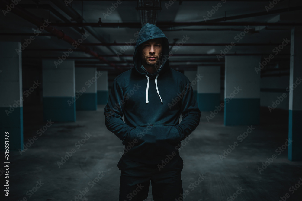 Fototapeta Serious attractive muscular caucasian sportsman in hoodie standing in underground garage with hands in pockets at night. Urban life concept.