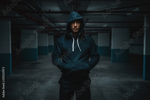 Foto Serious attractive muscular caucasian sportsman in hoodie standing in underground garage with hands in pockets at night