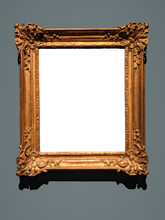 Blank Canvas Inside An Elaborate Golden Wooden Frame On A Gray Wall. Shadow On Top Of White Canvas And Below The Frame Matches The Lighting.