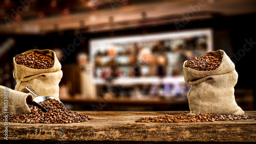 Wooden board of free space for your decoration and fresh coffee beans in brown sacks Canvas Print