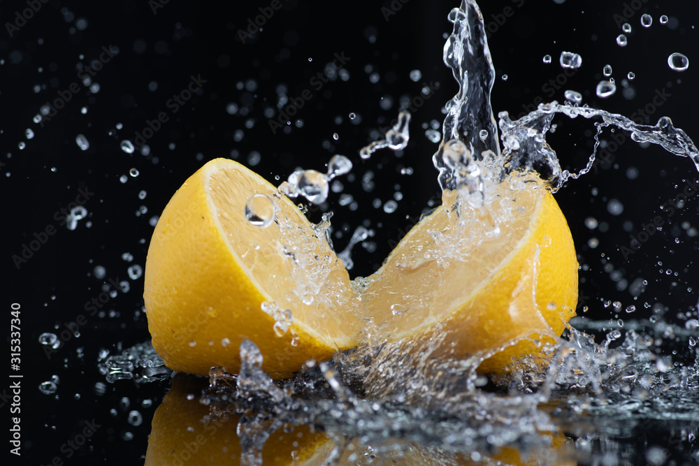Fototapeta halves of a whole lemon with drops and splashes of water on a black background