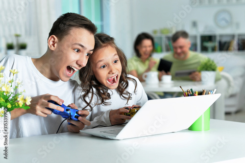 Boy and girl playing video game on laptop Wallpaper Mural