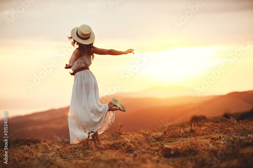 Happy woman standing with her back on sunset in nature Wallpaper Mural