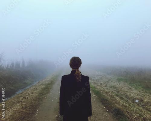 Leinwand Poster Una donna pensierosa nella nebbia nella ricerca di felicità