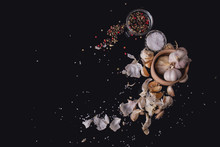 Garlic Cloves On Black Surface. Mix Of Allspice And Clove. Slt In Glass Cup. Black Studio.