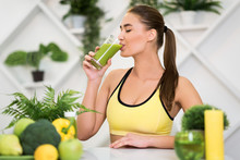 Young Woman Drinking Fresh Smoothie After Home Training