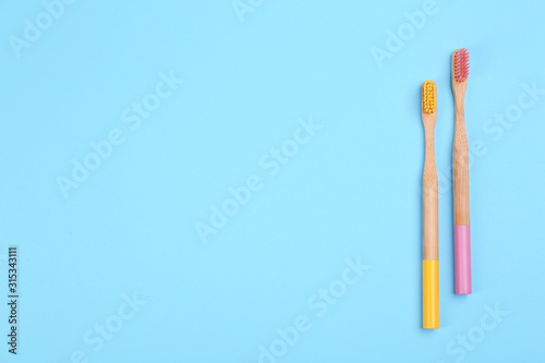 Obraz na plátně  Toothbrushes made of bamboo on light blue background, flat lay