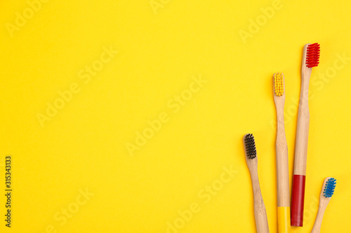 Fotografie, Obraz  Toothbrushes made of bamboo on yellow background, flat lay