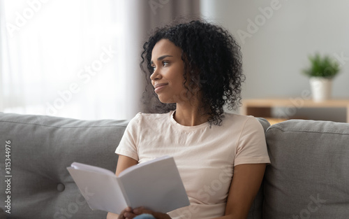 Fotografia  African woman distracted from reading looks out the window