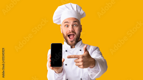 Obraz na plátně Excited Chef Man Showing Smartphone Screen Posing, Studio Shot, Panorama