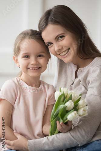 Fotografia Head shot portrait mother and little daughter with flowers vertical