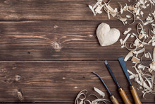 Wooden Heart With Wood Shavings And Instruments For Carving At Brown Rustic Dark Wooden Texture. Romantic Wood Craft Background.