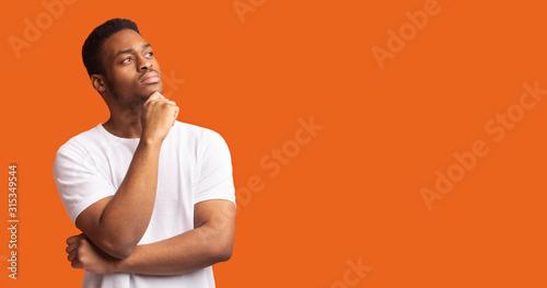 Pensive black man profile portrait on orange background