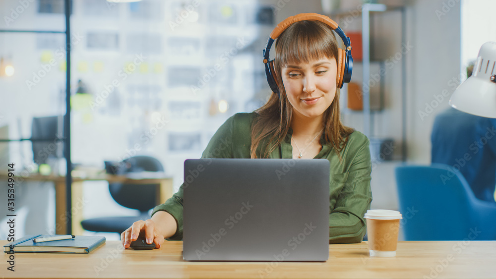 Fototapeta Young Beautiful Brunette Works on a Laptop Computer in Cool Creative Agency in a Loft Office. She is Wearing Headphones. She is Happy, Smiling and is Having Fun.