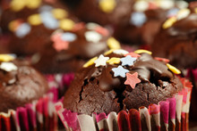 Homemade, Delicious Cocoa Muffins With Colorful Sugar Stars And Dark Chocolate Icing. Extreme Close Up, Shallow Depth Of Field And Selective Focus