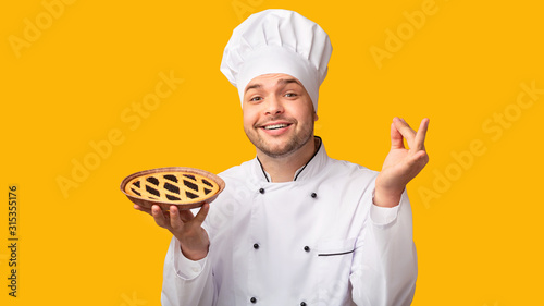 Fototapeta Happy Baker Showing Pie Standing On Yellow Background, Panorama
