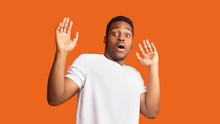 Terrified Afro Guy Over Orange Studio Background