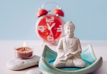 Finding Time For Self Care And Balance Between Body Soul And Mind. Balance Between Work And Home Concept. Lotus Pose White Color Sitting Meditation Buddha Figurine, Red Alarm Clock On Background.