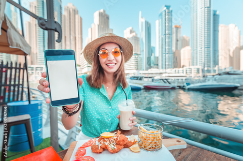 Asian girl eats seafood cuisine overlooking the skyscrapers and Marina port in Dubai and shows a blank screen of her smartphone Canvas Print