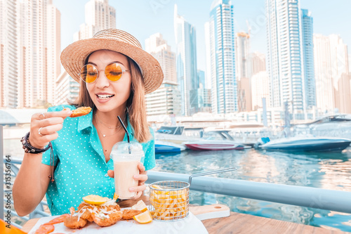 Photo Happy asian woman eats prawns in batter and French fries on the terrace of a sea
