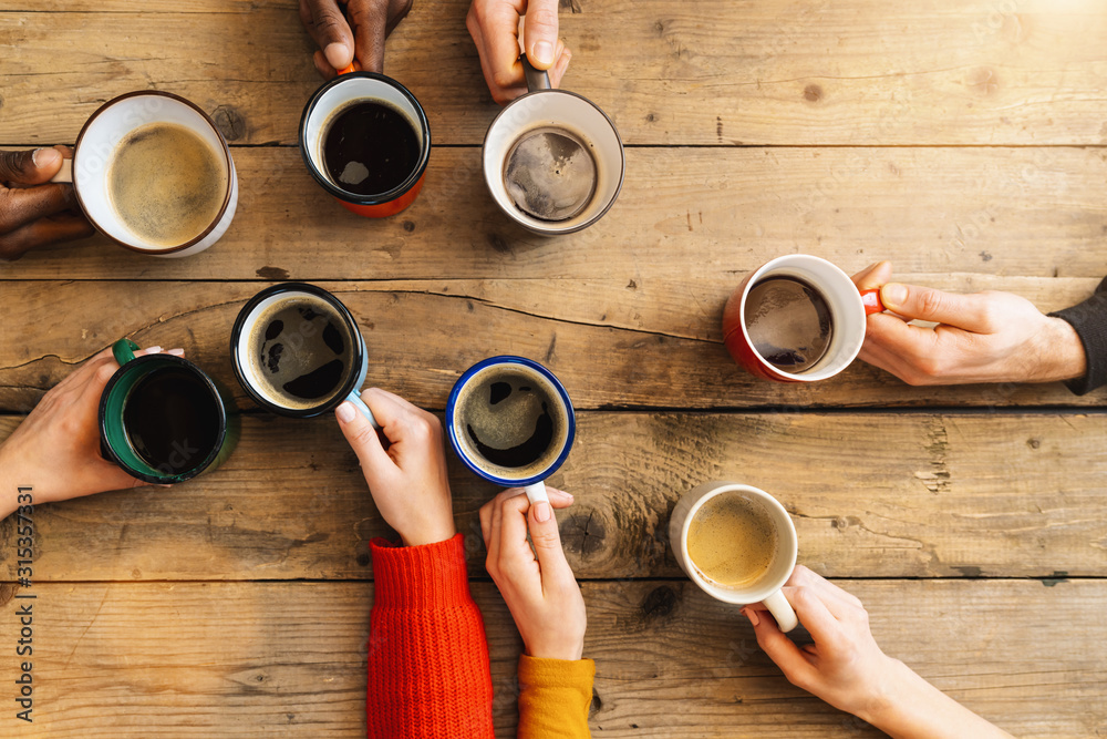 Fototapeta Friends group drinking coffee and cappuccino in a bar or restaurant - People hands cheering and toasting on top view point - breakfast together concept with white and black men and women
