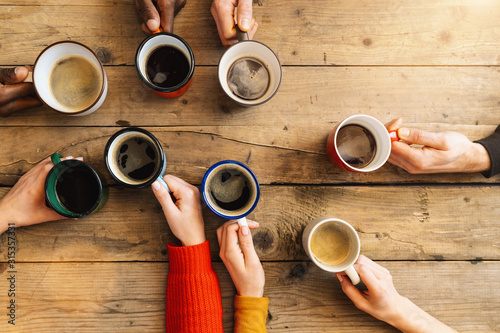 Fototapeta Friends group drinking coffee and cappuccino in a bar or restaurant - People hands cheering and toasting on top view point - breakfast together concept with white and black men and women obraz