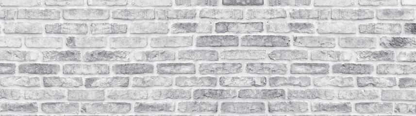 White washed shabby brick wall wide texture. Large light gray rustic brickwor...