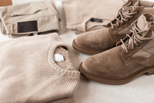 Fashionable Mens Autumn-spring Beige Suede Boots With A Stylish Knitted Sweater On A White Table. Trendy Classic Look In A Pastel Colors For Men. Fashion Seasonal Menswear And Shoes. Close-up.