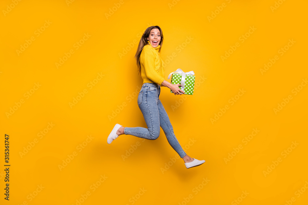Fototapeta Full length profile side photo of amazed crazy funky girl like holiday sales hold green dotted gift box bring boyfriend jump run wear casual style clothing isolated yellow color background