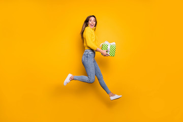 FototapetaFull length profile side photo of amazed crazy funky girl like holiday sales hold green dotted gift box bring boyfriend jump run wear casual style clothing isolated yellow color background