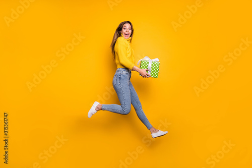 fototapeta na ścianę Full length profile side photo of amazed crazy funky girl like holiday sales hold green dotted gift box bring boyfriend jump run wear casual style clothing isolated yellow color background