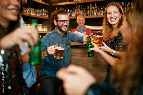 Small group of people standing at pub, chatting, drinking beer and enjoying friday night Wallpaper Mural