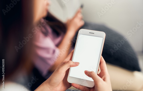 Obraz Woman hand holding smartphone with blank screen on sofa in house with friends. Take your screen to put on advertising. - fototapety do salonu
