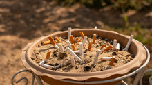 Close Up Picture Of Cigarette Butts Stuck In Ashtray