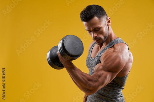Fotomural Muscular young man pumping up biceps
