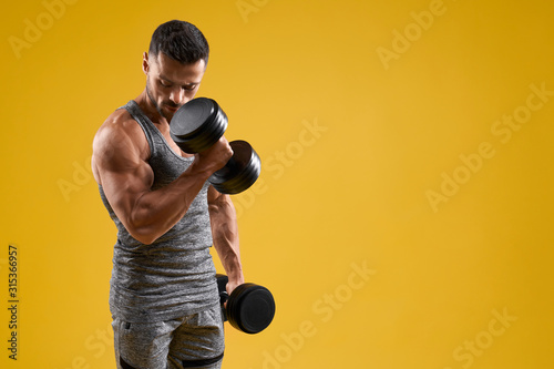 Strong bodybuilder working out with dumbbells Fototapeta