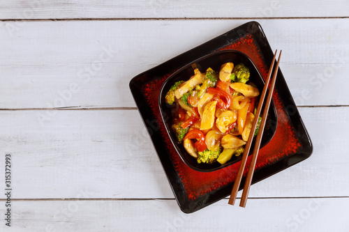 Asian stir fry meat with paprika, onion and broccoli in square bowl Wallpaper Mural