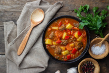 Goulash, Beef Stew Or Bogrash Soup With Meat, Vegetables And Spices In Cast Iron Pan On Wooden Table. Hungarian Cuisine. Rustic Style. Top View.