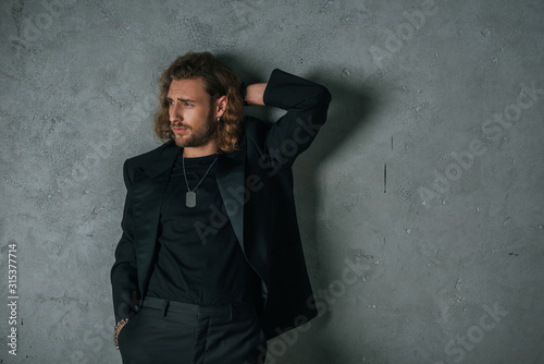 Fotomural fashionable businessman in black suit posing with hand in pocket and looking awa