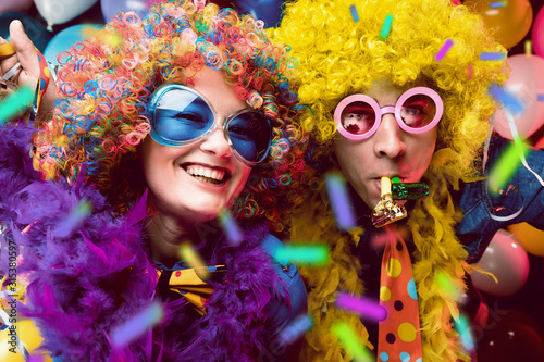 Obraz Women and men celebrating at party for new years eve or carnival. - fototapety do salonu