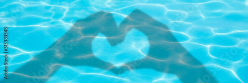 Shadows of hands forming a heart on blue swimming pool water background, panoramic valentines day or summer banner