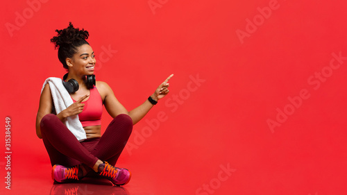 Obraz Cheerful fitness model sitting on floor, pointing at free space - fototapety do salonu