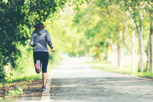 Leinwand Poster Sporty asian woman runner running and jogging through the road