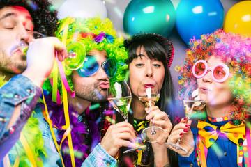 Glückliche Party Freunde feiern karneval und stoßen mit Sekt an.