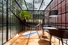 Modern Sunroom With A Hammock And Some Plants