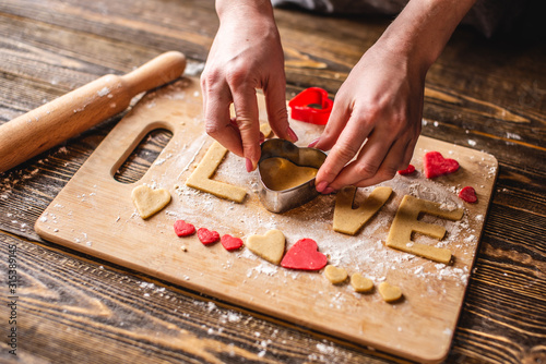 Fototapeta Cooking cookies from the dough in the shape of a heart and the word love. Baking for Valentine's day and a romantic date obraz