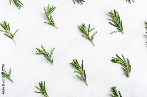 Natural wallpaper with aromatic rosemary twigs. Rosemary pattern on white marble background. Flat lay overhead composition.