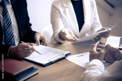 Obraz na plátně Employer or committee holding reading a resume with talking during about his pro