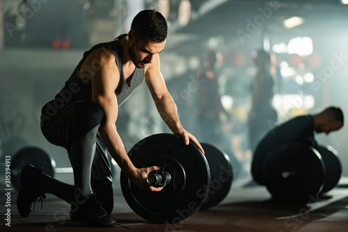 Young sportsman adjusting barbell on weight training in a gym. Wallpaper Mural